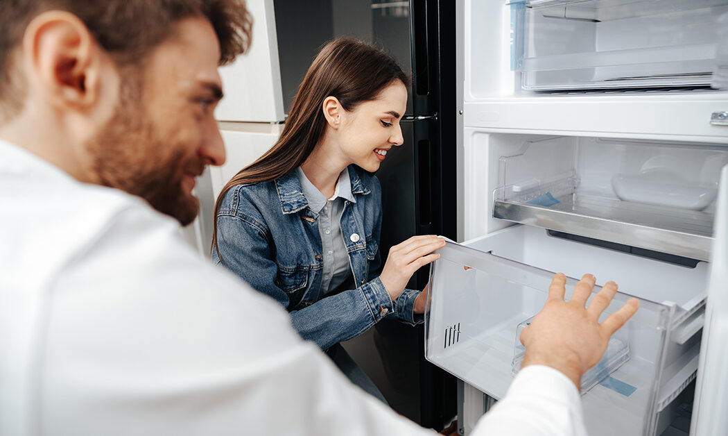 Young couple selecting new refrigerator in household appliance store